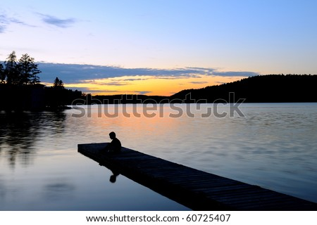 Young Boy Sitting on a Dock at Sunset