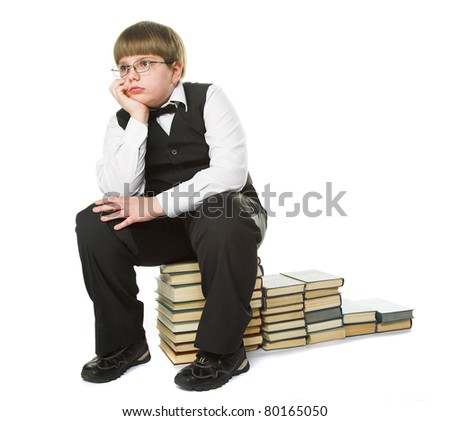 young boy sitting on the pile of old books