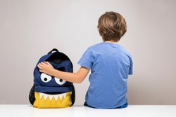 Young boy sitting on white desk with his cute school backpack, monster face bag with open pocket. Back to school