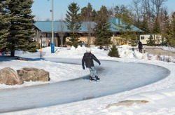 Young boy skating on an icy trail