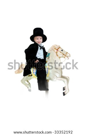 Young boy smiles happily as he rides his stallion into the sunset.  He is sitting on a carousel horse and wearing a tuxedo and top hat.