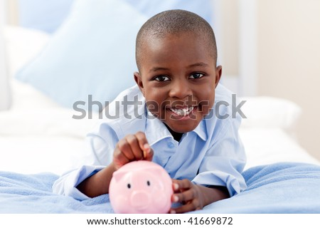 Young boy smiling at the camera while putting money into his piggy bank - stock photo