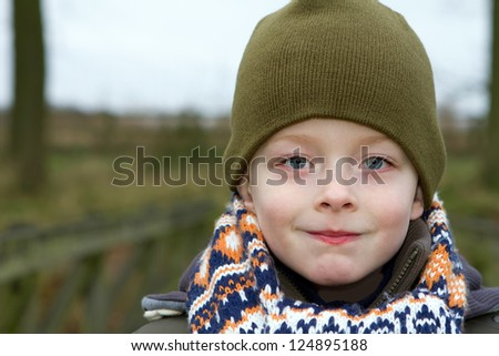 young boy smiling whilst outdoors in cold weather