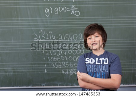 Young boy solving a maths problem in class standing with a piece of chalk in his hand in front of the blackboard covered in numbers #147465353
