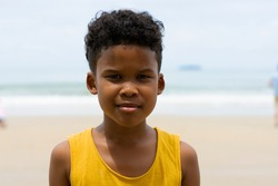 Young boy stand on the beach with happy mood. summer and vacation concept. Half of body composition.