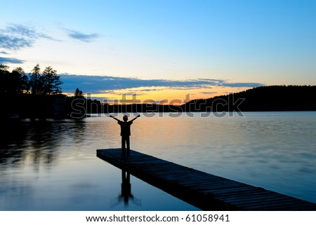Young Boy Standing and waving on a Dock at Sunset