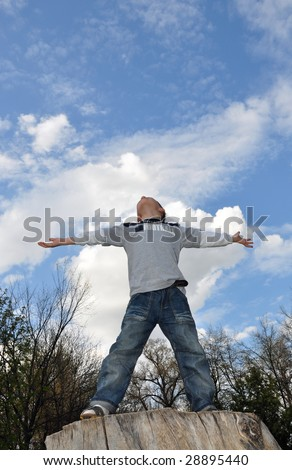 young boy standing on the top, sky is above