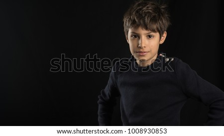 Young boy studio portrait against black background.
