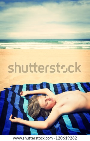 Young boy sunbathing on the beach. Cross procesing effects.