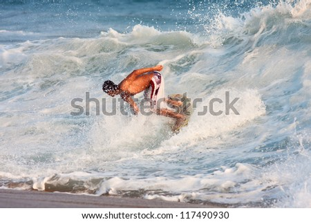 Young boy surfing on the wave