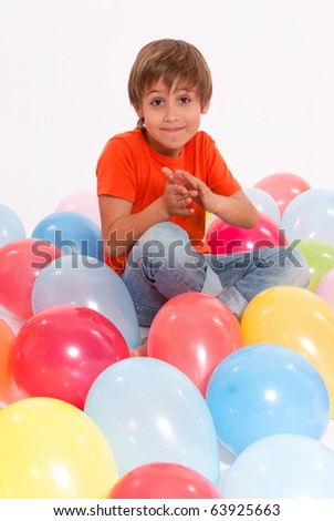 Young boy surrounded by colourful balloons