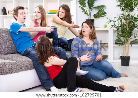 Young boy  switches the channel on TV, unsatisfied girls watching  him