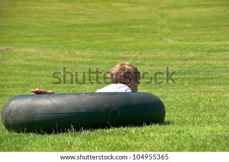 Young boy takes a nap in the tube on the lawn
