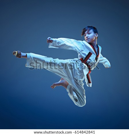 Young boy training karate on blue background Foto stock ©