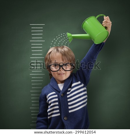 Young boy trying to make himself taller with watering can measuring his growth in height against a blackboard scale Foto stock ©
