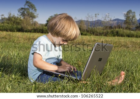Young boy typing on notebook, sitting on the grass