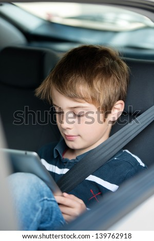 Young boy using a tablet computer while sitting in the back passenger seat of a car with a safety belt over his shoulder