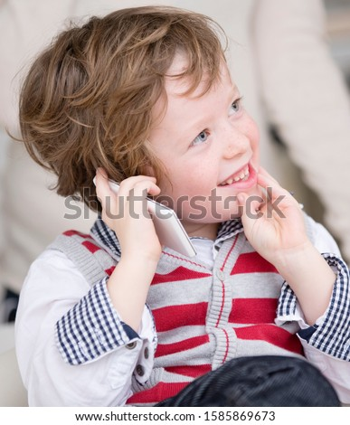 Young boy using cell phone, looking away