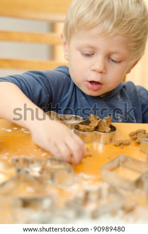Young boy using cutouts and mixing dough to make gingerbread cookies.