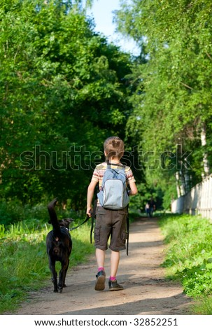 Young boy walking with black dog