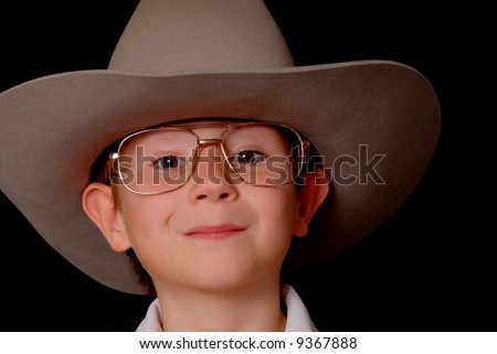 Young boy wearing a cowboy hat isolated on black #9367888