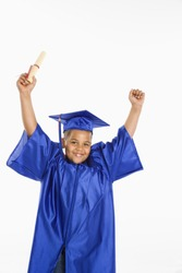 Young boy wearing blue graduation gown holding diploma and cheering.