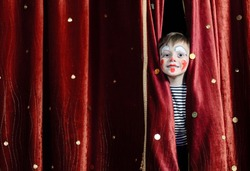 Young Boy Wearing Clown Make Up Peering Out Through Opening in Red Stage Curtains