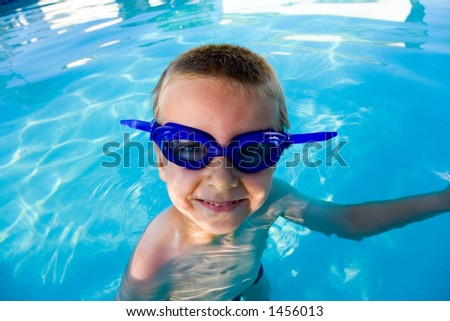 Young boy wearing diving mask or goggles in the swimming pool afternoon.