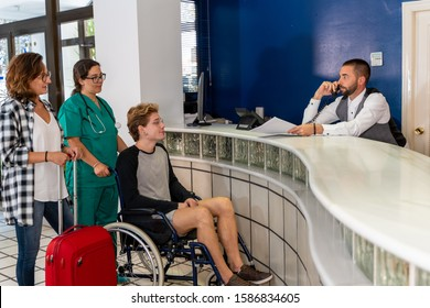 Stock photo of A young boy in a wheelchair accompanied by an nurse and a girl with a suitcase wait at a hospital reception while the receptionist talks on the phone