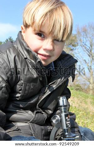 Young boy with a microscope outdoors