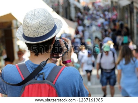 young boy with a straw hat photographs tourists in Venice #1237161985