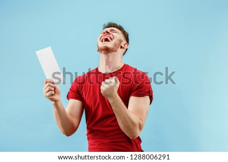 Young boy with a surprised happy expression bet slip on blue studio background. Human facial emotions and betting concept. Trendy colors