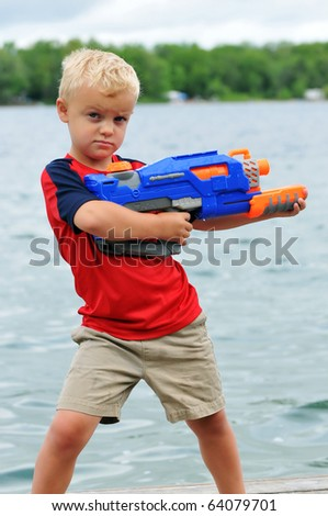 Young Boy with Attitude Holds a Water Gun