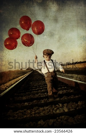 young boy with balloons on...