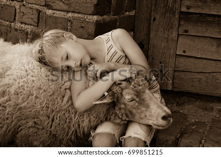 young boy with blonde hair wearing shorts and striped vest hugging a sheep. sheep holding her head on boy's lap. summertime in the summertime #699851215