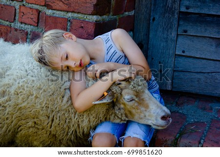 young boy with blonde hair wearing shorts and striped vest hugging a sheep. sheep holding her head on boy's lap. summertime in the summertime #699851620