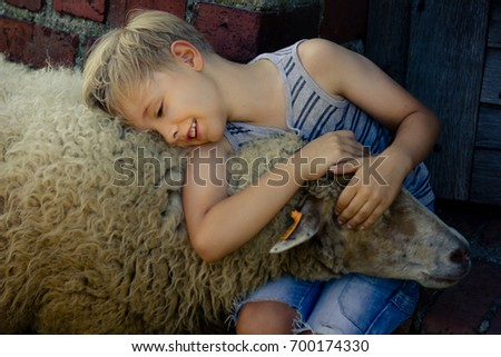 young boy with blonde hair wearing shorts and striped vest hugging a sheep. sheep holding her head on boy's lap. summertime in the summertime #700174330