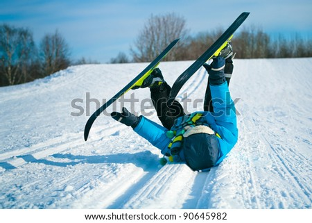 Young boy with cross-country skis lying on snow
