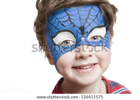 Young boy with face painting superhero smiling on white background
