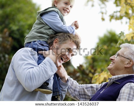 Young Boy With Father And Grandfather Enjoying Together In Park