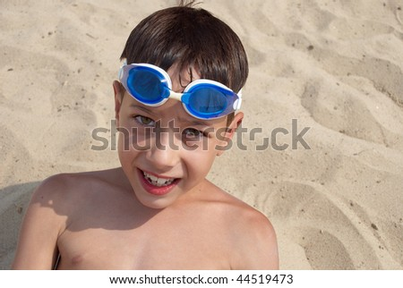 Young boy with goggles for swimming is in the sand