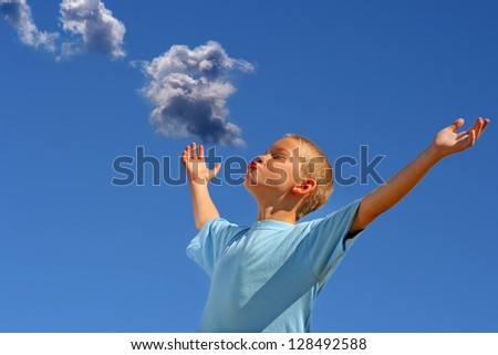 Young Boy with hands up on the Blue Sky and Cloud Background