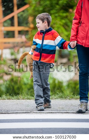 Young boy with his mother by the crosswalk