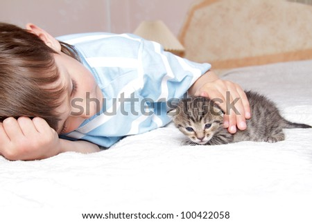 young boy with kitten at home - stock photo