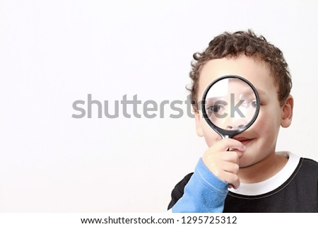 young boy with magnifying glass ready to explore stock photo