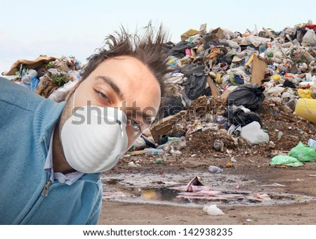 Young boy with mask respiratory protection near landfill