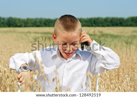 Young boy with mobile phone in the summer wheat field