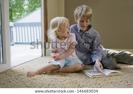 Young boy with sister sitting on carpet with book laughing