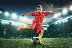 Young boy with soccer ball doing flying kick at stadium. football soccer players in motion on green grass background. Fit jumping boy in action, jump, movement at game. Collage