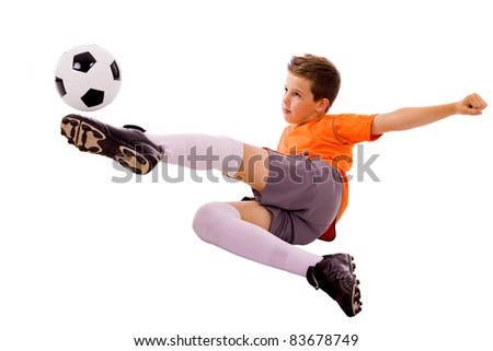 Young boy with soccer ball doing flying kick, isolated on white